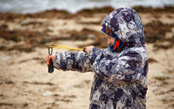 A boy in a jacket on the sand shoots with best slingshot ammo