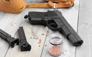 Air pistol, two clips, holster and balls for shooting at a wooden table.
