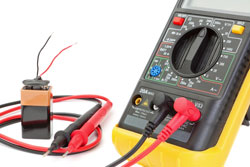 Electrical multimeter to check the resistance. on a white wall with battery