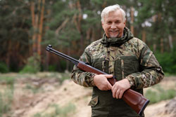 Happy hunter old man in camouflage with .177 airgun
