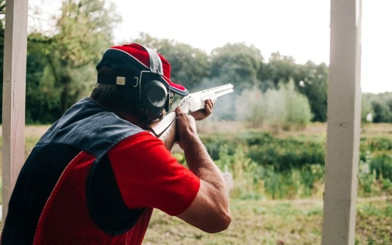 Hunter shoots with a shotgun on a target in special clothes and headphones