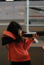 Little girl in red hoodie holding black bb rifle