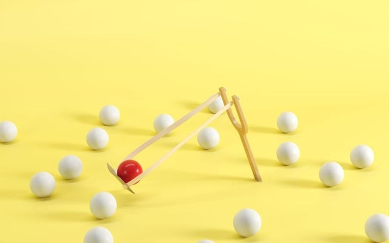 Outstanding red ball in a slingshot surrounded by white balls on yellow background