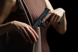 Woman hand pulling a best air pistol for self defense out of handbag