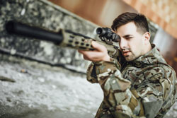 A military soldier targets and holds a large rifle in the building