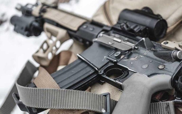 An assault rifle lies on a military briefcase.