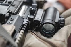 An assault rifle lies with an eye on a military briefcase