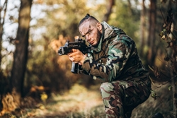 Camouflage soldier with rifle and painted face playing airsoft outdoors in the forest