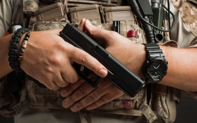 Close-up of a man pulls a gun from his holster