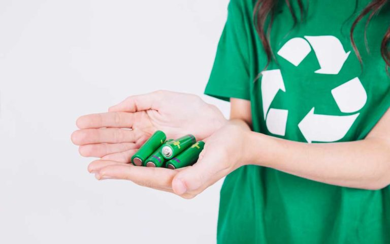 Close-up of a woman's hand holding green batteries