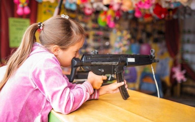 Girl shoots from children's toy gun in children's entertainment center