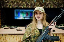 Girl with machine gun at hands on shooting range
