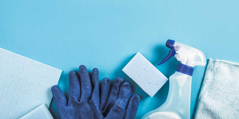 High angle view of spray bottle, gloves and sponge on blue background