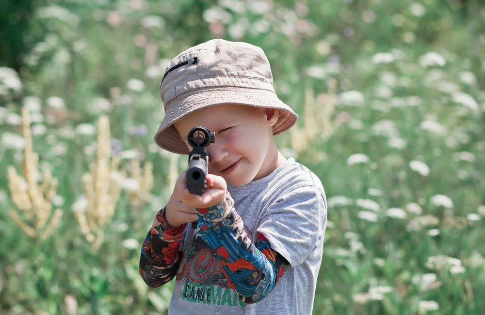 Little boy with toy gun at hunt outside
