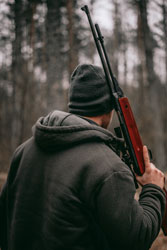 Man with airgun rifle in a forest
