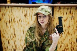 Military girl in camouflage uniform with revolver gun at hand against army background on shooting range