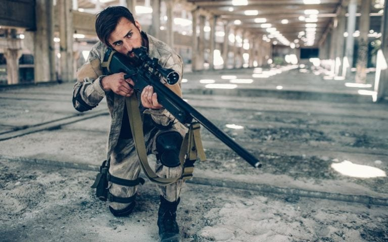 One dark-haired man is standing in long hangar by himself. he has put one knee down on the ground and holding rifle in hands