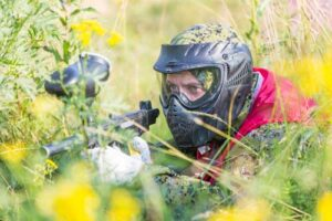 Paintball sport player in protective uniform and mask playing with gun outdoors and sneaking in grass