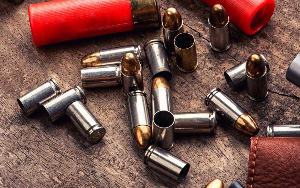 Pistol gun bullets and magazine strewn on wooden