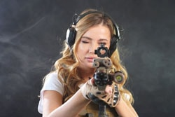 Pretty girl in an airsoft uniform and headphones poses against a dark background with smoke in the background