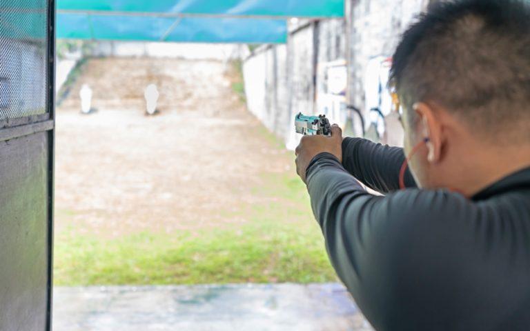 Rear view of a man shooting with gun at target in shooting range