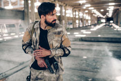 Serious man is standing in hangar and holding paintball gun in hands