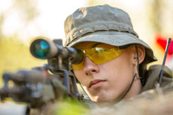 Sniper armed with large caliber, sniper rifle, shooting enemy targets on range from shelter, sitting in ambush