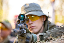 Sniper armed with large caliber, sniper rifle, shooting enemy targets on range from shelter