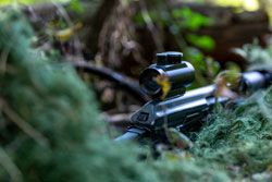 Special forces, soldier assault rifle with silencer, optical sight. behind cover waiting in ambush