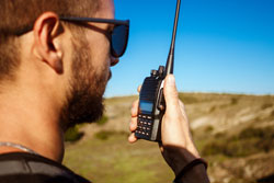 Young handsome man talking on walkie talkie radio