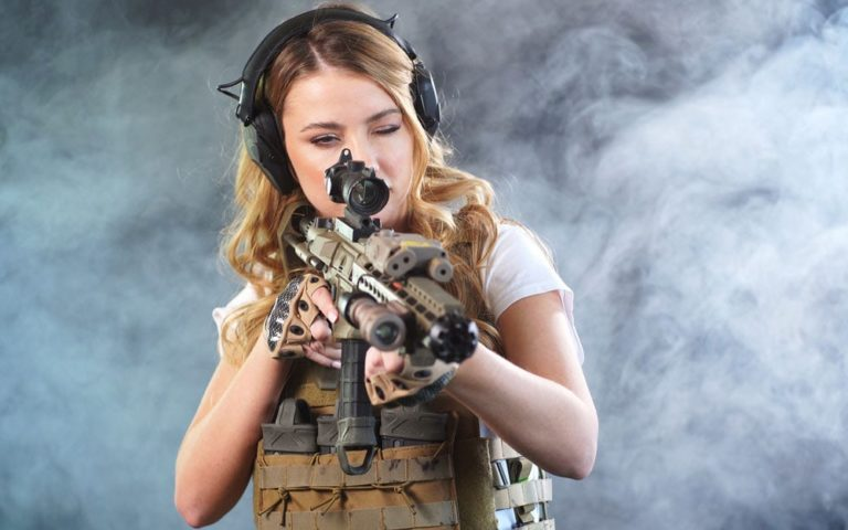 Young woman dressed for airsoft points a sniper rifle at the target