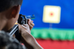 ear view of man with his gun on shooting at the target