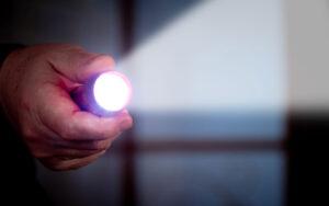 A man holds a flashlight in dark room