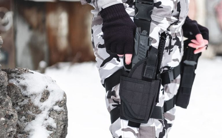 A military man in camouflage and gloves takes out a pistol from a holster