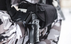 A pistol in a holster on a military foot