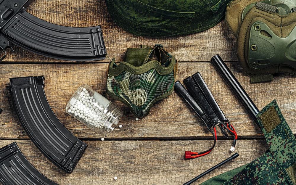 Airsoft gun magazines and airsoft balls on wooden surface Premium