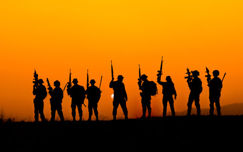 Silhouette of soldier team in sunset sky