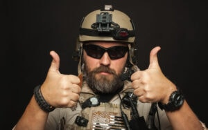 Brutal man in military uniform shows two fingers
