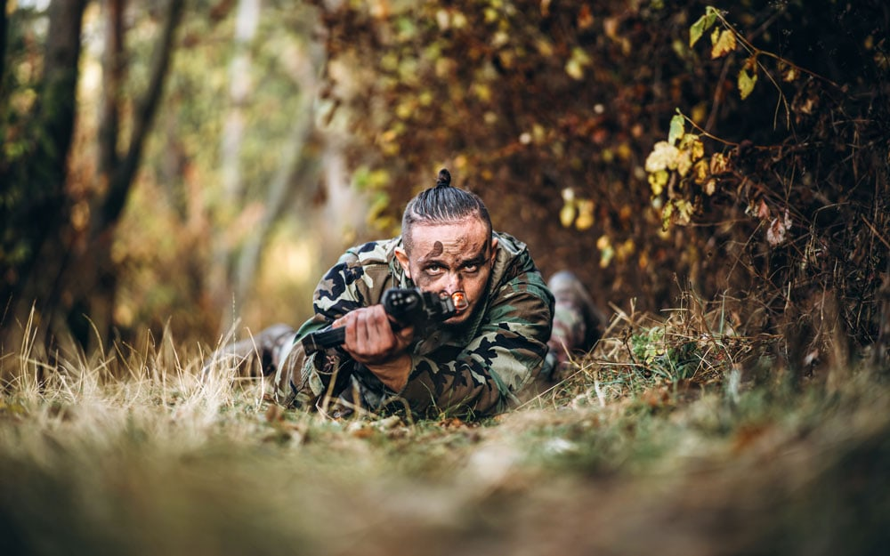 Camouflage soldier with rifle and painted face lying in the grass aiming at the rifle