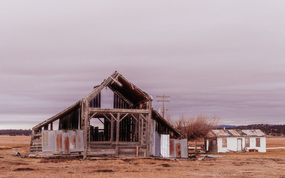 Half-built large wooden structure in a dry desert field with grey