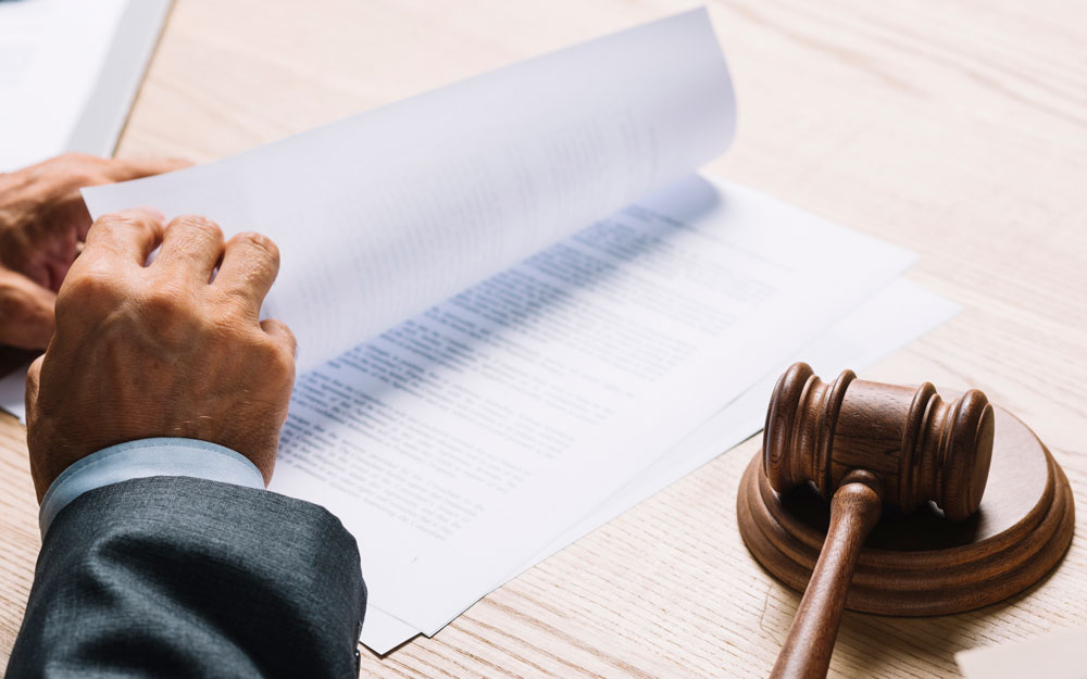 Male lawyer turning the documents in a courtroom