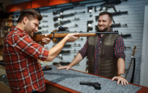 Man aims with new rifle, seller at counter in gun shop