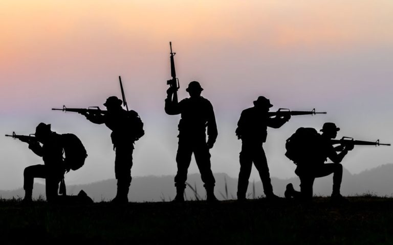 Military or soldier silhouettes on sunset sky background
