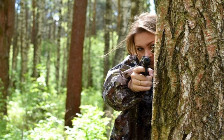 Military woman shoots with a gun in forest
