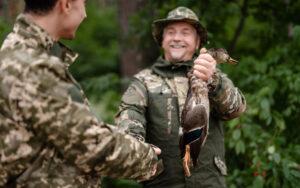 Proud hunter holding wild duck men handshaking