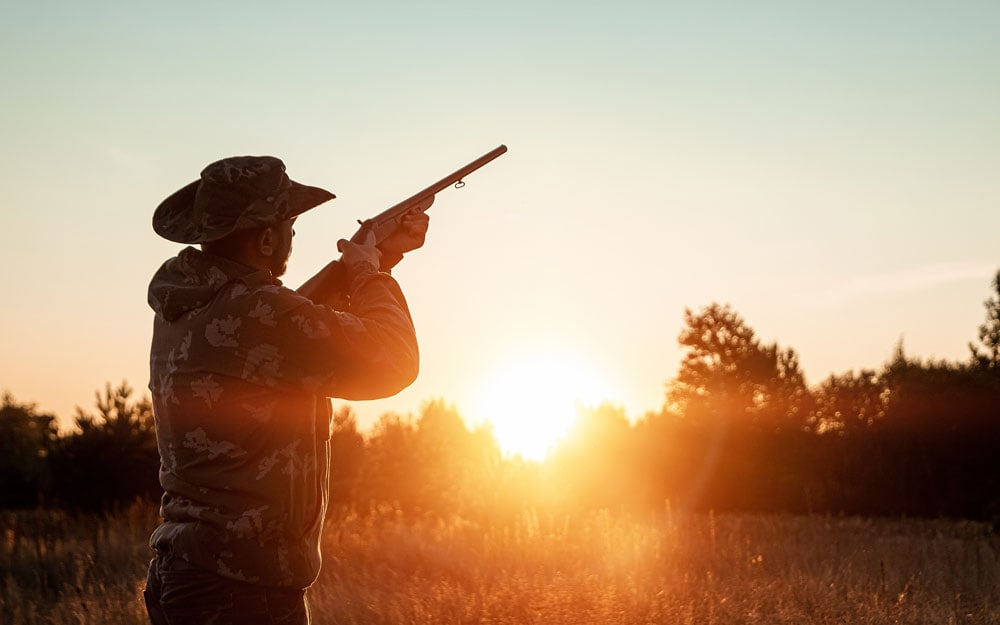 Silhouette of hunter in a cowboy hat with a gun in his hands on a beautiful sunset