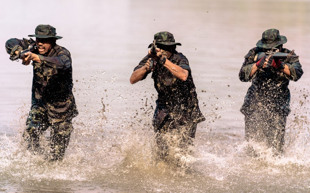 Team of soldiers running in the water