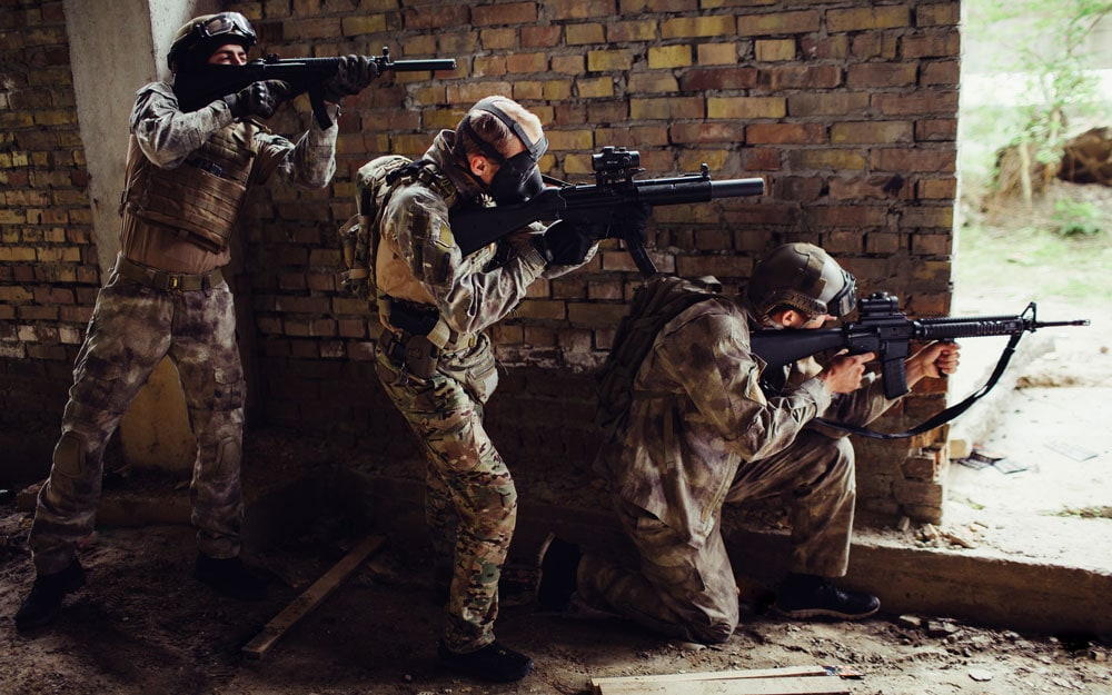 Three guys in ammunition are standing and hiding behind wall