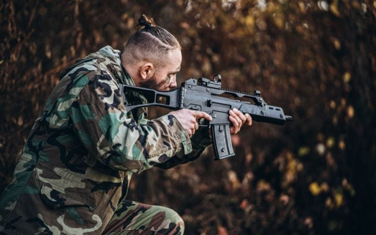 soldier with rifle and painted face playing airsoft outdoors in the forest