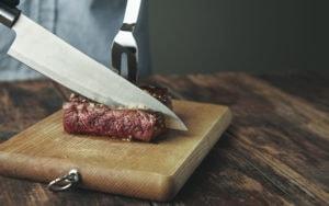 Knife cut slice of grilled meat on wooden board